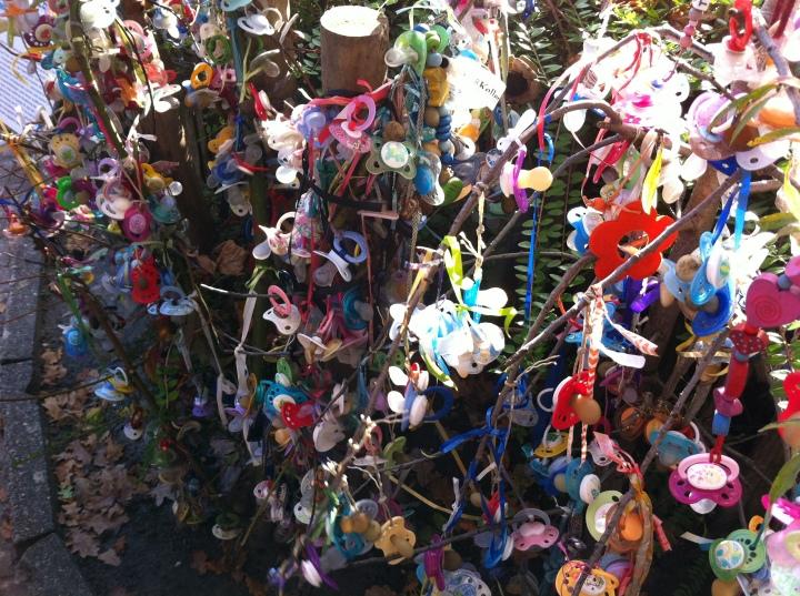 Kinderen nemen afscheid van hun speentje door 'm in de Schnullerbaum van Aken te hangen